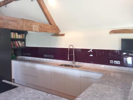 Coloured glass splashback aubergine colour kitchen