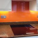 brightly coloured glass splashbacks match to RAL red orange kitchen